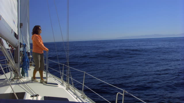 WS Woman standing on deck of yacht, looking out to sea and moving away / Santa Barbara, California, USA