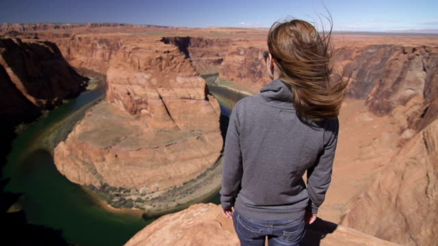 woman standing on edge of grand canyon, starring into it - grand canyon stock videos & royalty-free footage