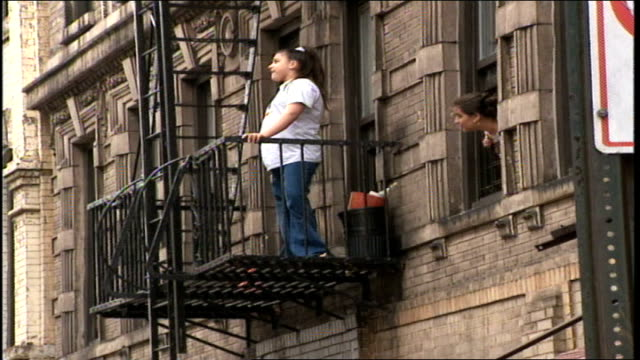 woman standing on fire escape people walking on street nyc - fire escape stock videos & royalty-free footage