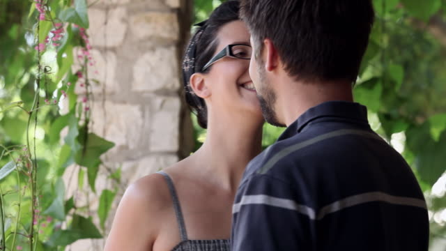 CU R/F woman standing on front porch of home looking out boyfriend walks in to give her a kiss