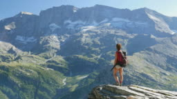 Woman standing on mountain top on the Alps, slow motion