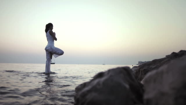 hd: woman standing on one leg in the sea - on one leg stock videos & royalty-free footage