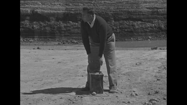 Woman standing on porch watching excavation / two shots of men in excavation site using drilling machines / man pushes plunger down / two shots of...