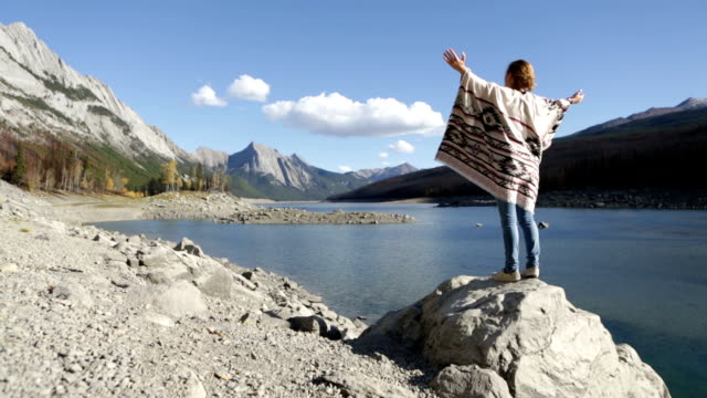 Woman standing on rock above lake, arms outstretched
