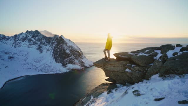 woman standing on rock and lookin at seaside of lofoten island in snow - snowcapped mountain stock videos & royalty-free footage