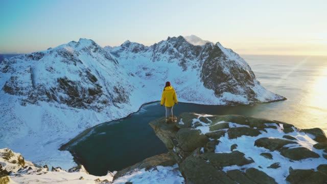 岩の上に立って、雪の中でロフォーテン島の海辺を見ている女性 - レインコート点の映像素材/bロール