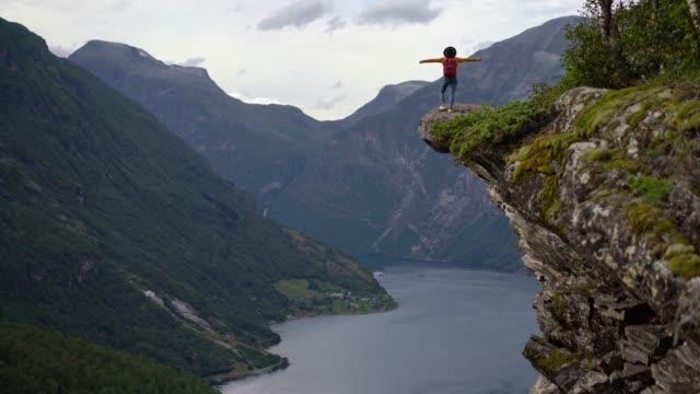 vídeos de stock e filmes b-roll de woman standing on rock near geirangerfjord in norway - norte