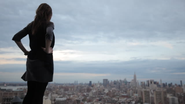 woman standing on rooftop overlooking manhattan - hand on hip stock videos & royalty-free footage