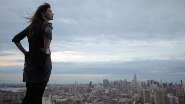 vídeos de stock, filmes e b-roll de woman standing on rooftop overlooking manhattan - telhado