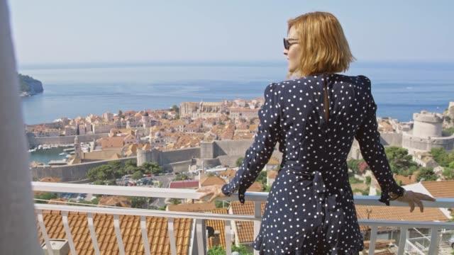 MS Woman standing on sunny balcony overlooking Dubrovnik,Croatia