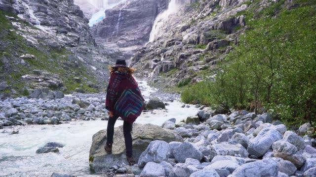 frau steht auf dem hintergrund des gletschers in norwegen - nationalpark stock-videos und b-roll-filmmaterial
