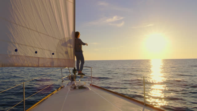 slo mo woman standing on the bow of a sailboat at sunset - ship's bow stock videos and b-roll footage