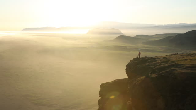 vidéos et rushes de a woman standing on the edge of a cliff overlooking the ocean. - cliff