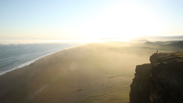 a woman standing on the edge of a cliff overlooking the ocean. - active seniors stock videos and b-roll footage