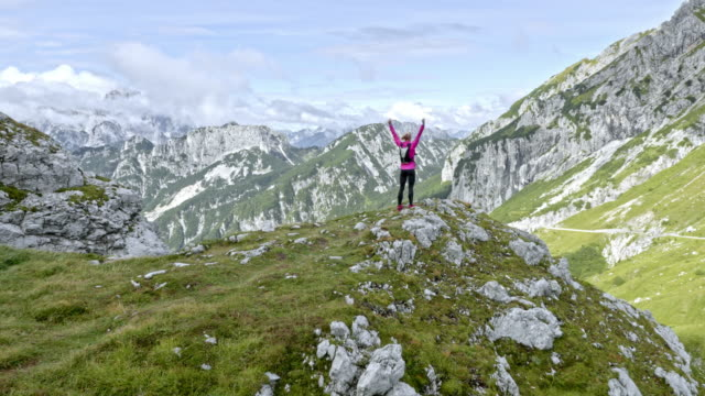 AERIAL Woman standing on the mountain top with her hands raised high in the air above the sunny valley