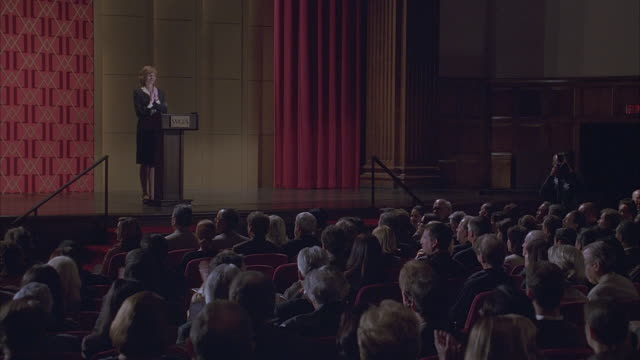 a woman standing on the stage in an auditorium. - lectern stock videos & royalty-free footage