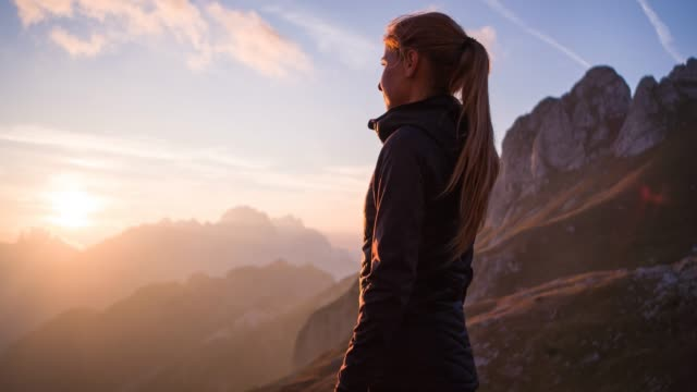 woman standing on top of mountain, enjoying breathtaking view at sunset - guardare in una direzione video stock e b–roll