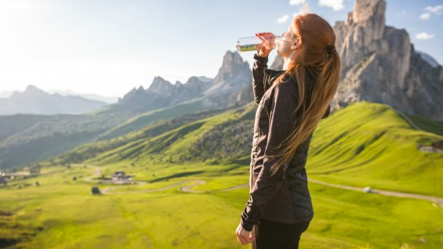 woman standing on top of mountain overlooking valley, drinking from a reusable water bottle - bottiglia video stock e b–roll