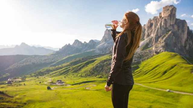 woman standing on top of mountain overlooking valley, drinking water - bottiglia d'acqua video stock e b–roll