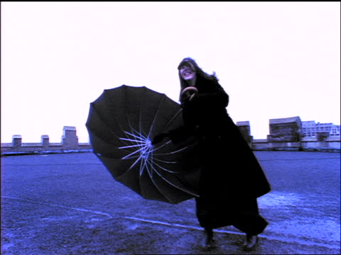 vídeos de stock e filmes b-roll de blue woman standing on windy rooftop holding umbrella + laughing / nyc - chapéu