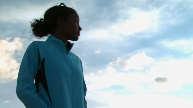 woman standing outdoors with blue sky and clouds - andere clips dieser aufnahmen anzeigen 1147 stock-videos und b-roll-filmmaterial