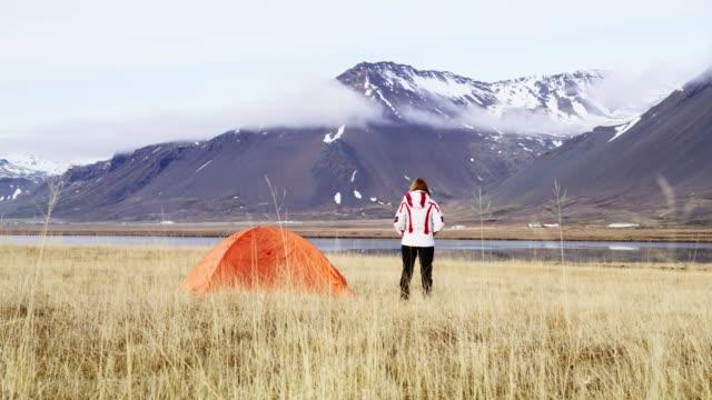 vídeos de stock e filmes b-roll de ws woman standing outside camping tent in remote mountain landscape,iceland - remote location