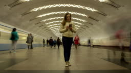 Woman Standing Still in Metro Station and Using Mobile Phone. Crowd of People and Passing Trains
