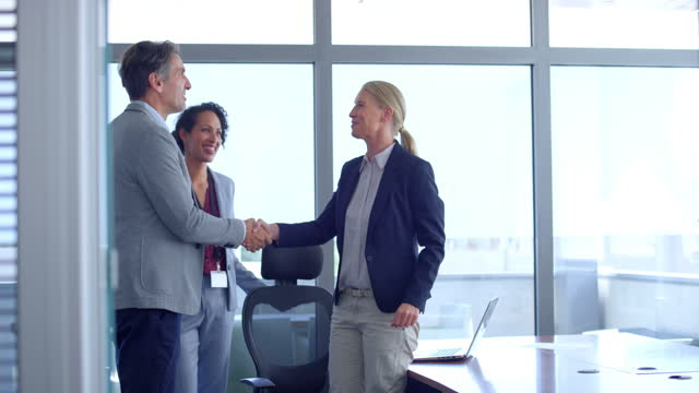 slo mo woman standing up to greet a man walking into the meeting room - businesswear stock videos & royalty-free footage