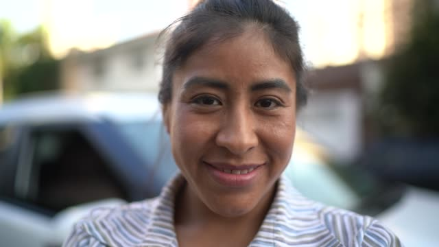 woman standing with arms crossed in front of a car in the street - peruvian ethnicity stock videos & royalty-free footage