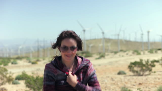 MS Woman standing with arms out in desert, wind turbines in background / Palm Springs, California, USA