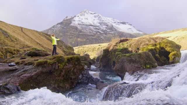 MS Woman standing with arms outstretched at Skogafoss waterfall,Iceland
