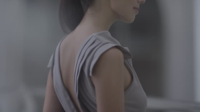 woman standing with her bag over left shoulder is turning and looking to her sides. - bag点の映像素材/bロール