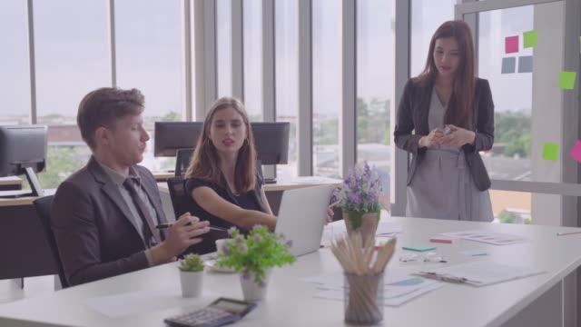 プレゼンテーションボードを持って立っている女性.民族的に多様なビジネスと、会議のスターについてビジネスパートナーと話したり、会ったりしています。パートナーの概念、ブレーンス - 討論点の映像素材/bロール
