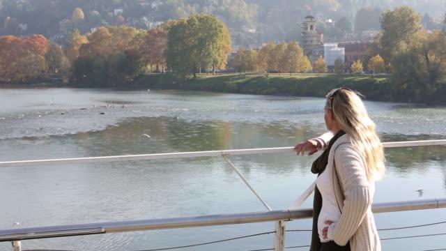 vidéos et rushes de woman stands at rail of bridge above river, looking out - une seule femme d'âge moyen
