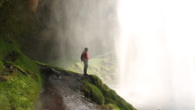 Woman stands behind tall waterfall with mist in Iceland
