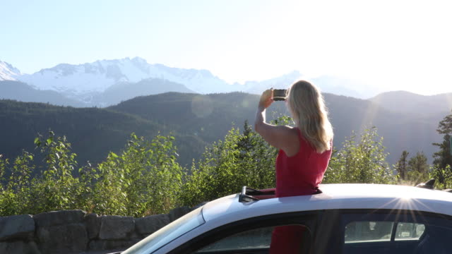 woman stands in car's sunroof, takes smart phone pic of mountain scene - sunglasses stock videos & royalty-free footage