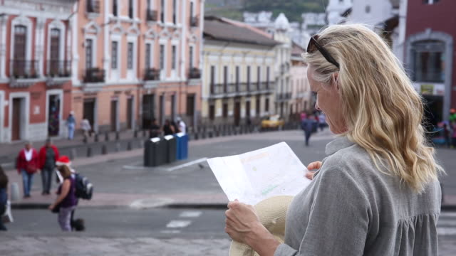 Woman stands in city piazza, holding map