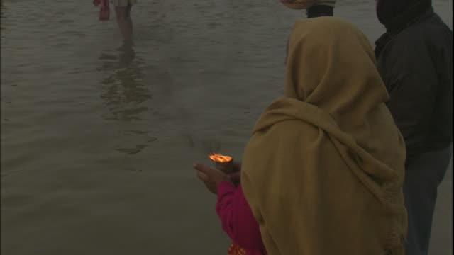 woman stands in ganges and prays with votive candle during kumbh mela, india - votive candle stock videos and b-roll footage