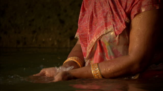 Woman stands in Ganges dipping hands in water Available in HD.