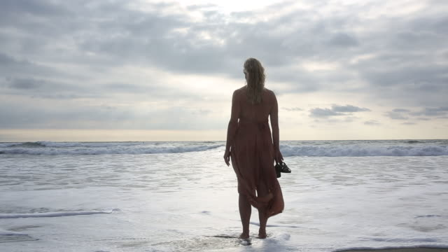Woman stands in gentle surf wearing dress, looks out to sea