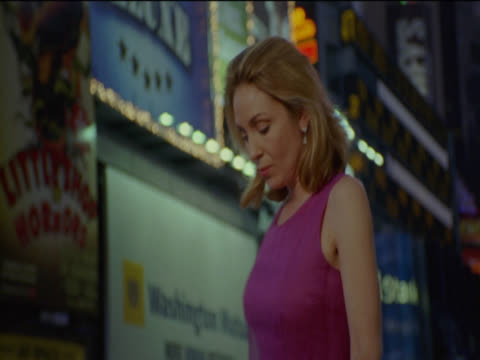 woman stands in time square, new york, looking around at the view and smiling, illuminated billboards in the background - hand an der hüfte stock-videos und b-roll-filmmaterial