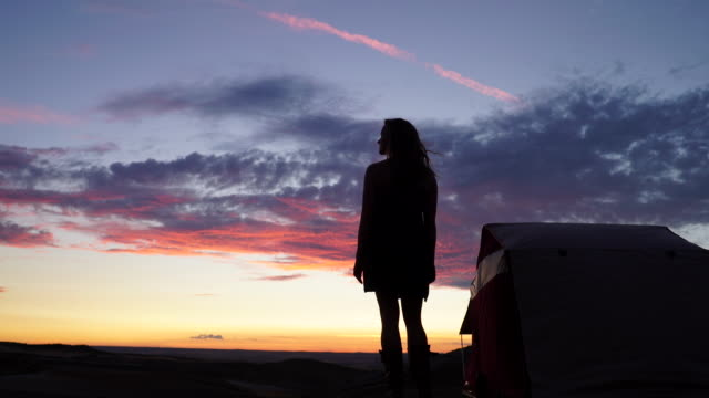 Woman stands next to roof tent watching the sunset
