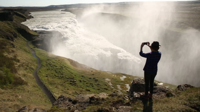 Woman stands on a trail overlooking a waterfall in Iceland and takes a photo