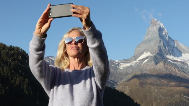 Woman stands on hillside with smart phone, Matterhorn distant