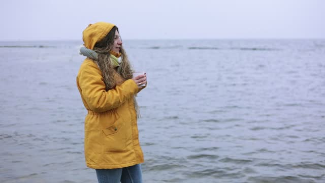 a woman stands on the shore of a large lake with a cup of hot tea in her hands. - 30 34 years stock videos & royalty-free footage
