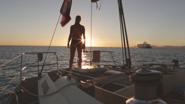 WS A woman stands on the stern of a sailing boat watching sunset / Ibiza, Spain