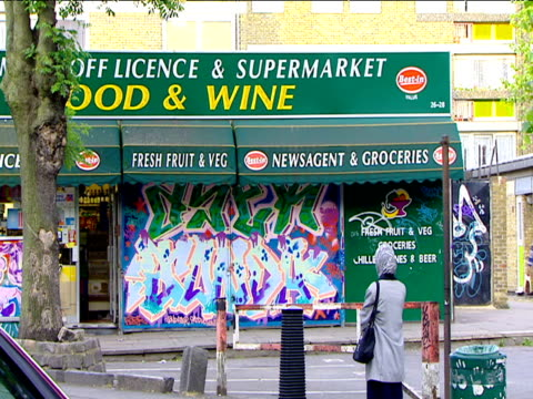 vídeos de stock e filmes b-roll de woman stands outside graffiti covered convenience store london - vendas
