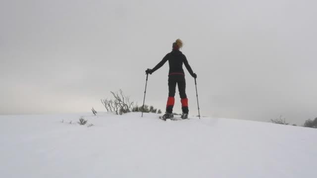 vídeos y material grabado en eventos de stock de woman stands over the mountain looking at the horizon - chaqueta de esquiar