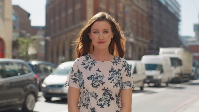 vidéos et rushes de ms a woman stands smiling to camera / london, united kingdom - la vingtaine