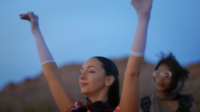 woman stands with eyes closed and hands raised to the wind as friend watches the sun set on desert road trip. - formal glove stock videos & royalty-free footage